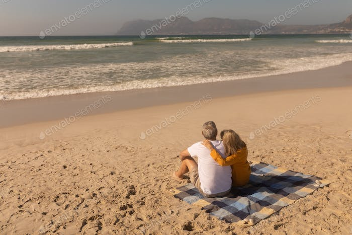 Rear view of senior couple relaxing on picnic blanket at beach