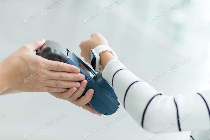 Woman pay by smartwatch by NFC technology