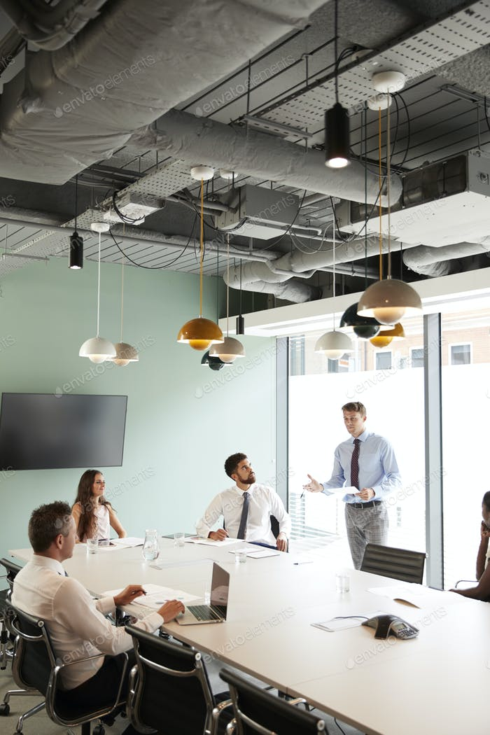 Businessman Giving Boardroom Presentation To Colleagues In Meeting Room