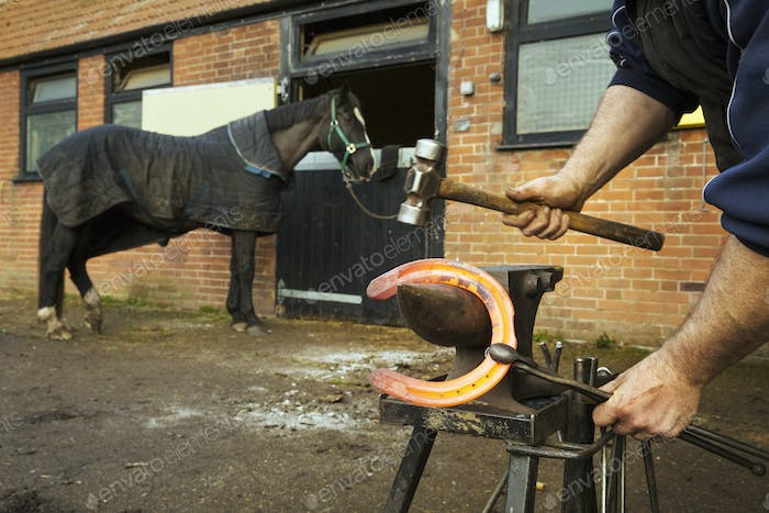 A farrier using tongs and hammer to hold and shape a red glowing heated metal horseshoe to be
