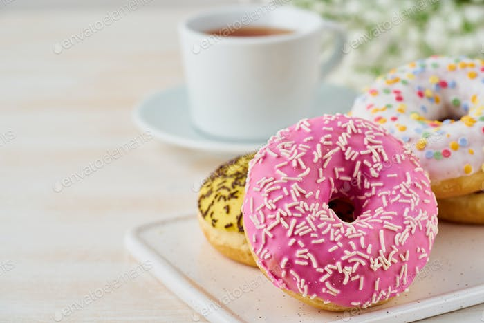 Doughnuts and tea. Bright, colorful junk food. Light beige wooden background. Side view, close up.