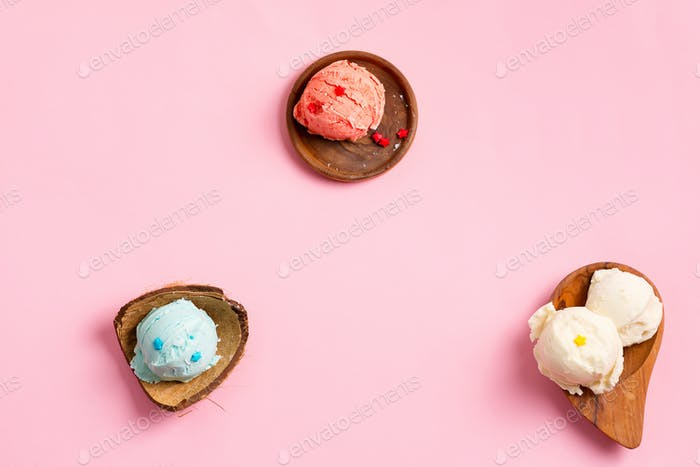 wooden plates with fresh natural colorful ice-cream on a pastel pink background
