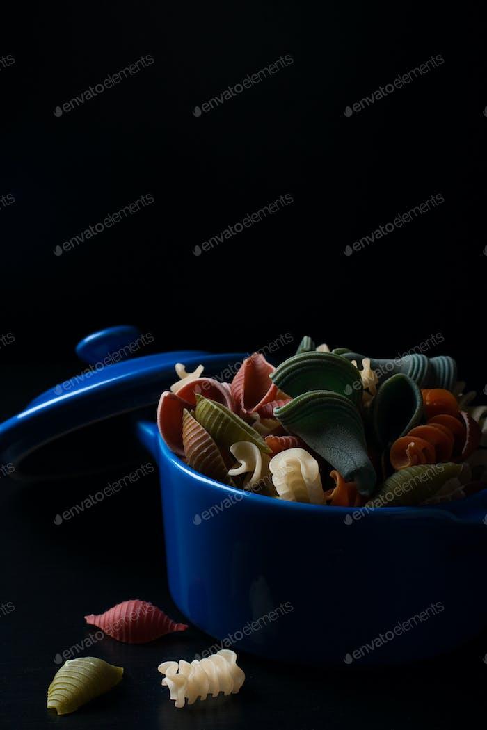 Farbige Dinkelnudeln in blauem Keramiktopf