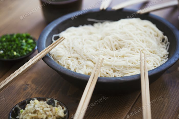 High angle close up of bowl with noodles and pairs of wooden chopsticks on a table.
