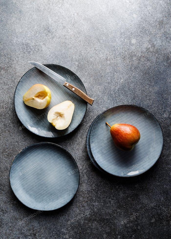 Blaues Keramik-Set mit Tellern und Birnen auf grauen strukturierten Hintergrund