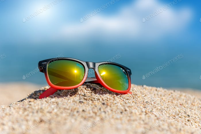 Mirrored sunglasses close up on the beach sand