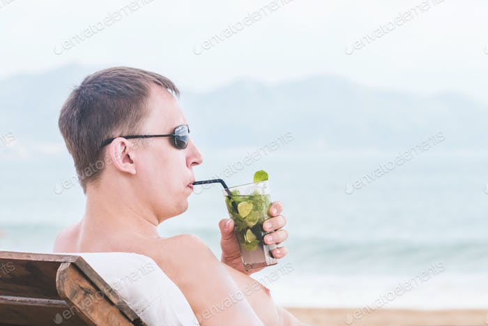 man in a sunglasses drink a cocktail