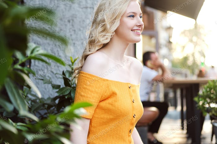 Side view of beautiful cheerful blond girl happily looking away in courtyard of cafe