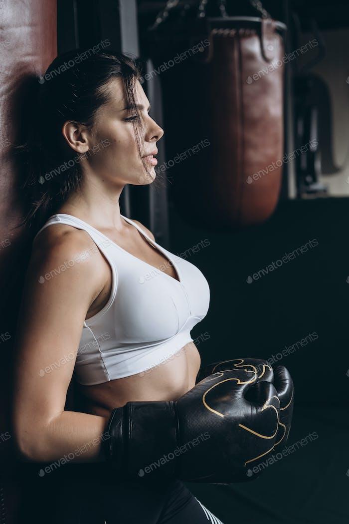 Boxfrau posiert mit Boxsack, auf dunklem Hintergrund. Starkes und unabhängiges Frauenkonzept