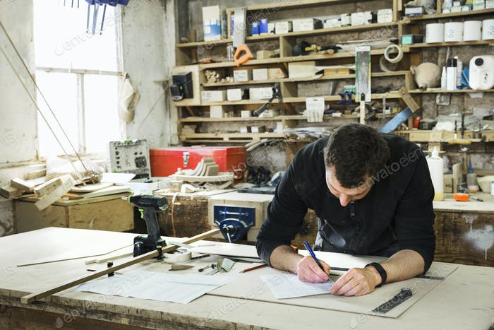 Man standing at a work bench in a carpentry workshop, writing a spreadsheet.