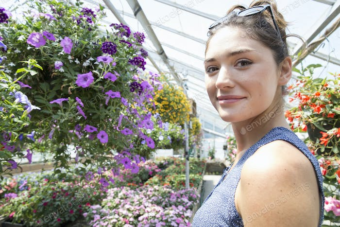 A woman standing surrounded by flowering plants in a commercial greenhouse.