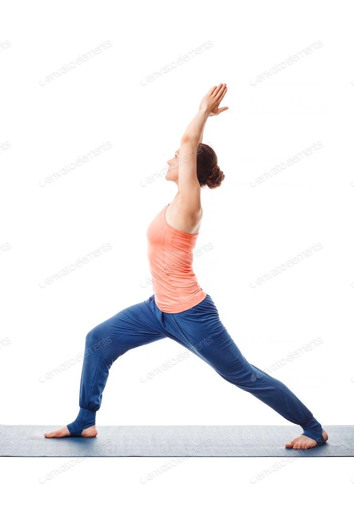 Woman practices yoga asana utthita Virabhadras