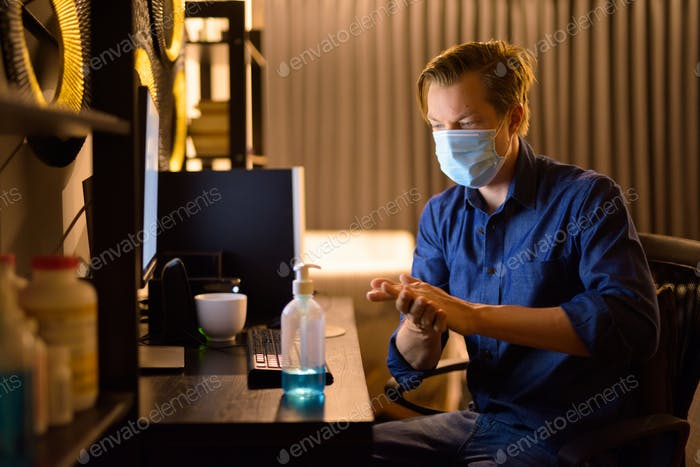 Young businessman with mask using hand sanitizer while working from home at night