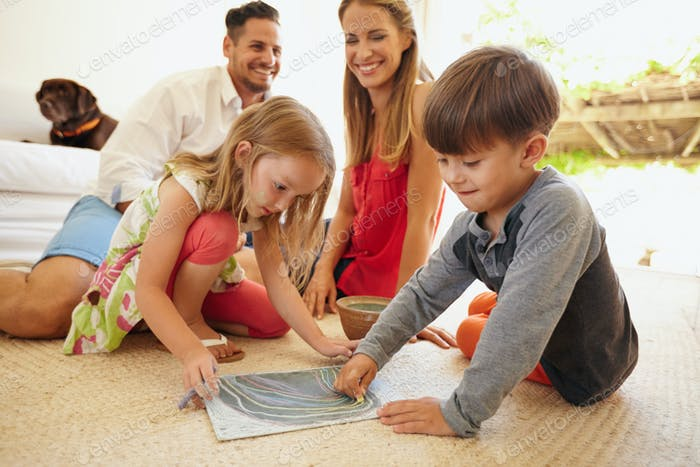 Children drawing with their parents in living room