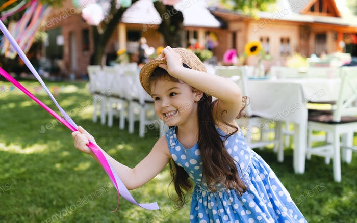 Small girl outdoors in garden in summer, playing with balloons