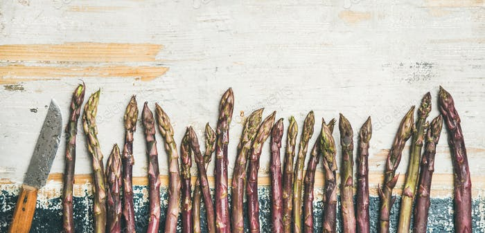 Fresh Raw purple asparagus over rustic wooden background, copy space