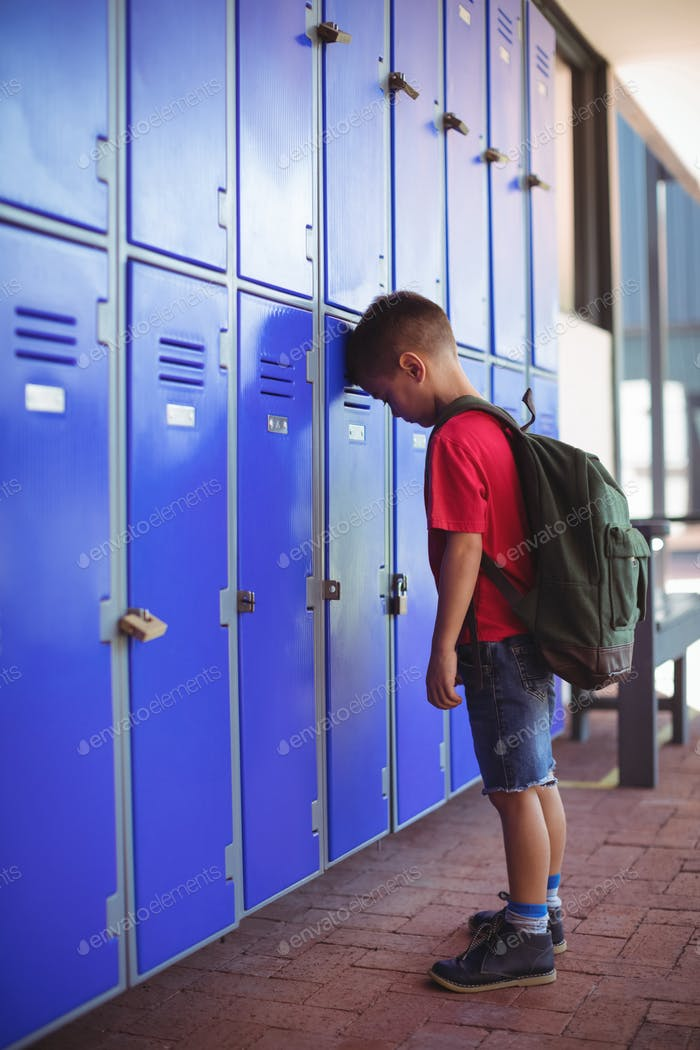 Side view of boy leaning on lockers in corridor
