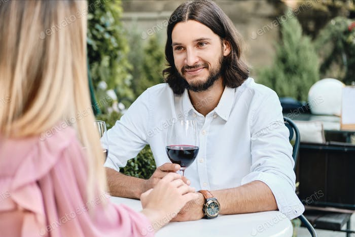 Young latin man with glass of wine happily looking at girlfriend on romantic date in cafe outdoor