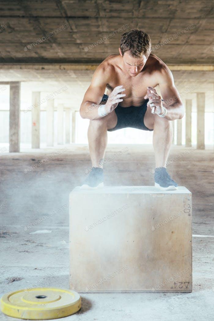 Muscular man doing box jumps