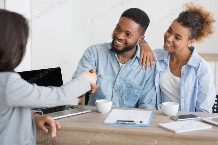 Smiling afro spouses handshaking with insurance broker in office