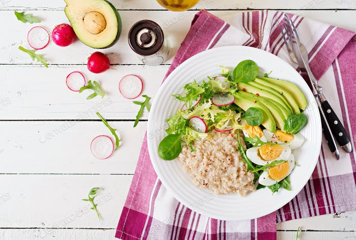 Healthy breakfast. Dietary menu. Oatmeal porridge and avocado salad and eggs. Top view