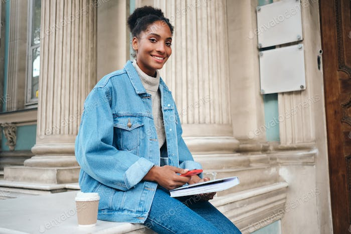African American student girl in denim jacket with cellphone and book happily looking in camera
