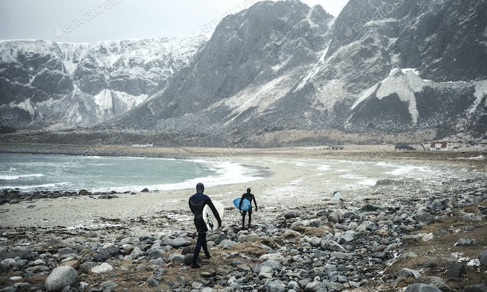 Two surfers wearing wetsuits and carrying surfboards walking along a beach with mountains behind.
