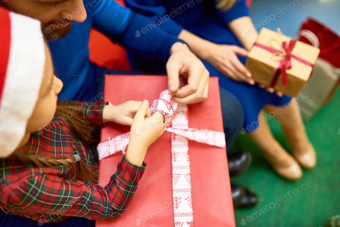 Girl opening present withparents
