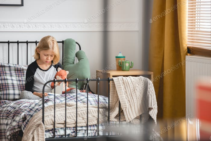 Cute little girl sitting on her single metal bed in trendy bedroom interior for child