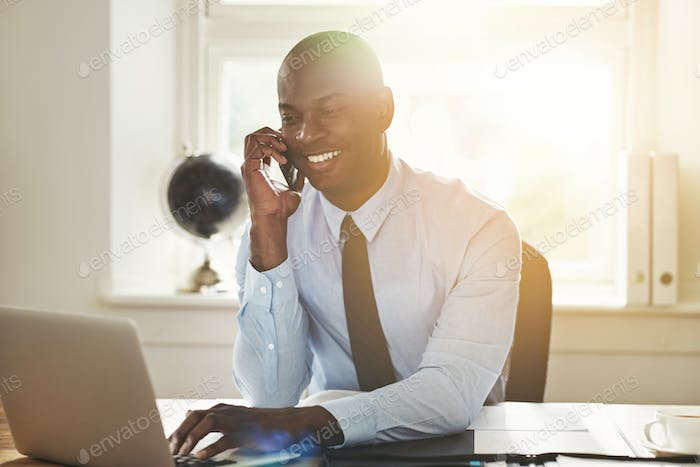 Smiling young businessman talking on a cellphone at work