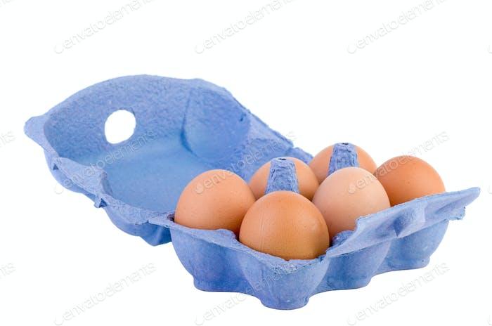 Cardboard egg box with six brown eggs