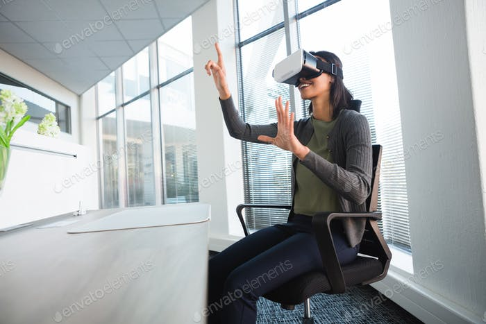Female executive using virtual reality headset at desk