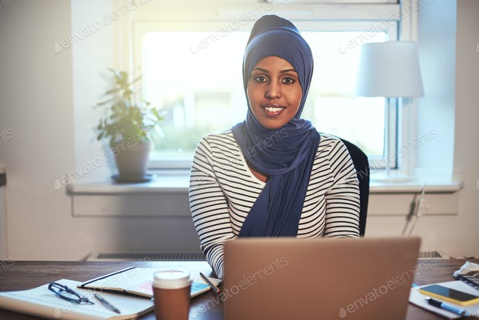 Smiling Arabic female entrepreneur working at home on a laptop