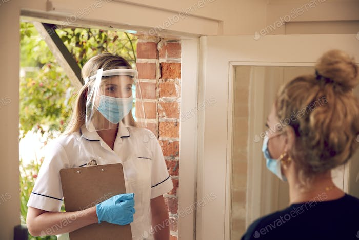 Female Health Worker Wearing Mask And Visor Visiting Woman At Home
