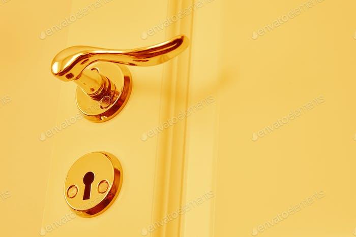Металлическая классическая дверная ручка в теплых тонах. Закрыто. Горизонтальная