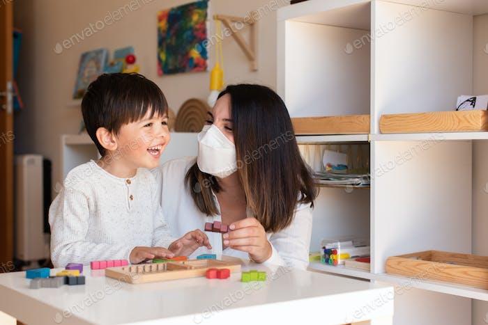 Kid jugando el rompecabezas de madera tetris con el profesor educador ayuda a usar la máscara facial para la pandemia de coronavirus.