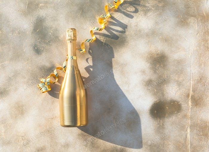 Flasche Goldener Champagner auf dem festlichen Hintergrund.