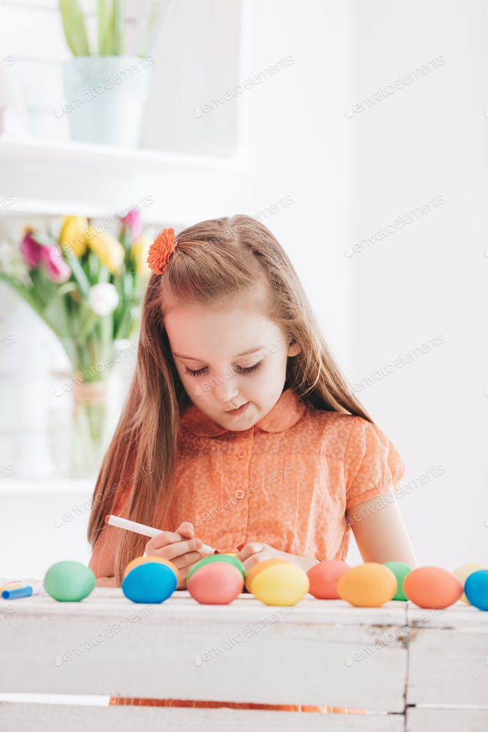 Young focused girl drawing patterns on dyed eggs
