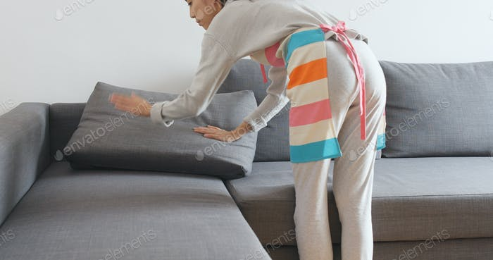 Housewife tidy up sofa couch at home