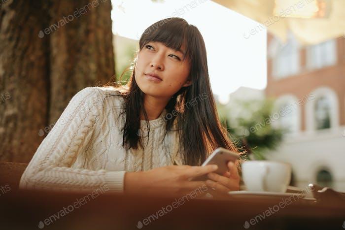 Thumbnail for Schöne junge asiatische Frau im Freien Café
