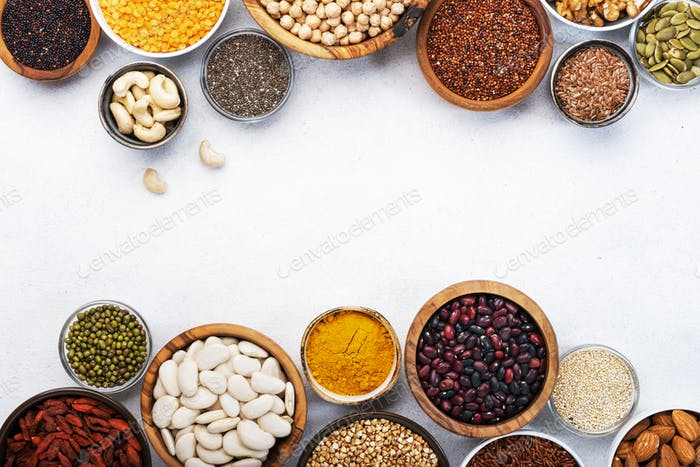 Various superfoods, legumes, cereals, nuts, seeds in bowls on white