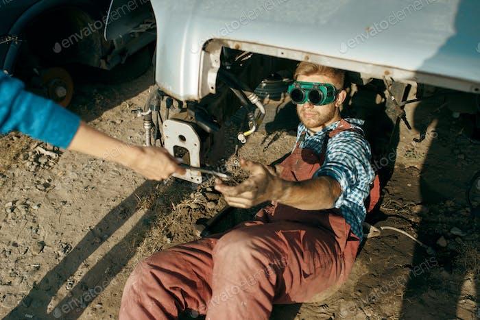 Male mechanic in welding glasses on car junkyard