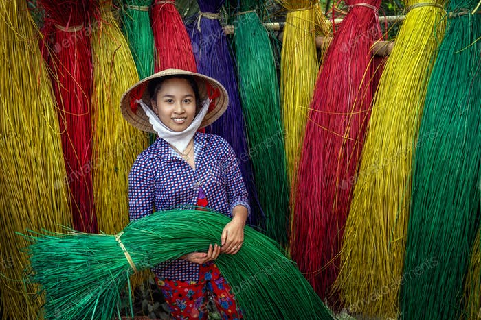 Portrait of Vietnamese female craftsman drying traditional vietnam mats