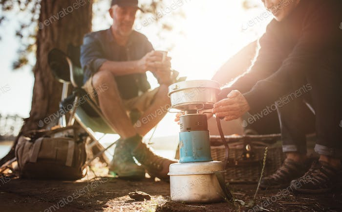 Woman warming hands on stove at campsite