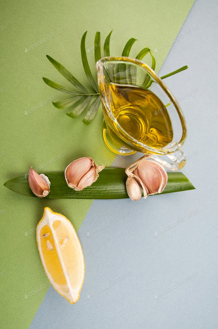 Cloves of garlic, slices of lemon and olive oil on blue-green te