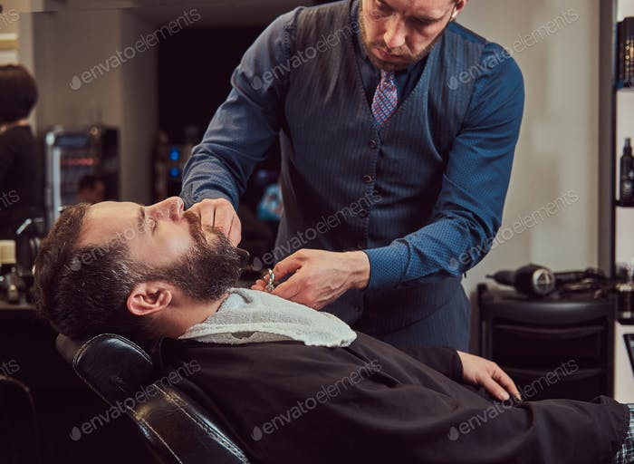Professional hairdresser modeling beard with scissors and comb at the barbershop.