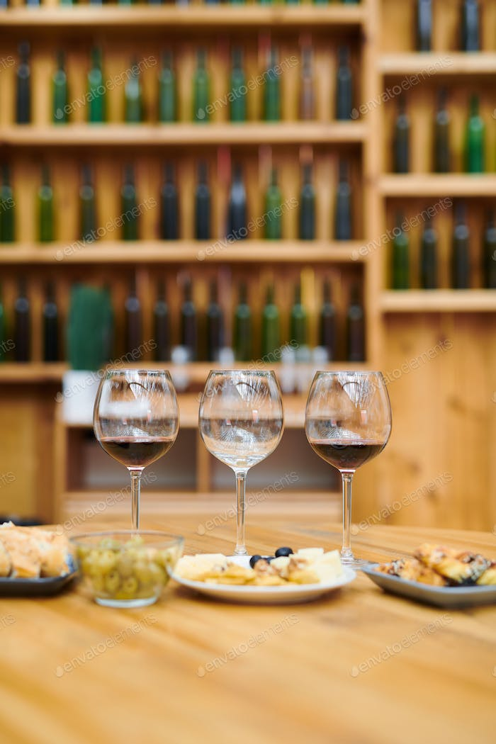 Three wineglasses and snack for sommelier on wooden table