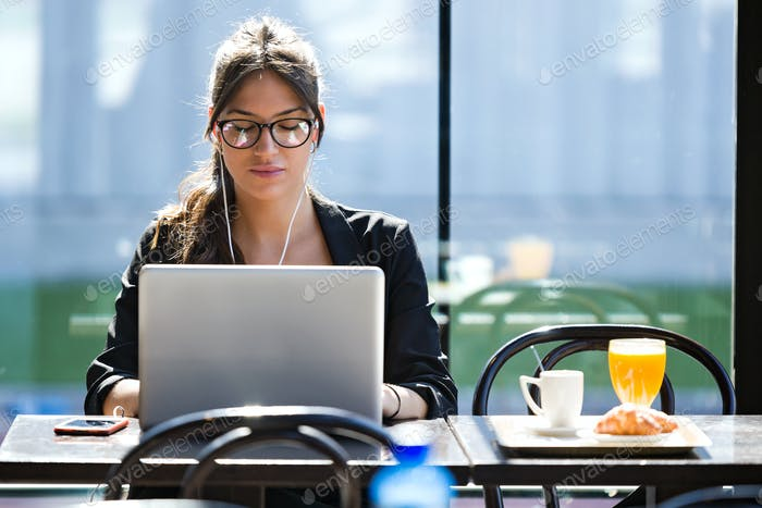 Beautiful young woman working with her laptop while having break