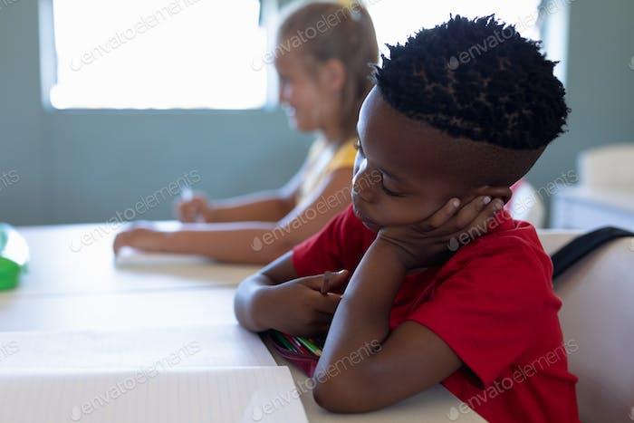 Schuljunge sitzt an einem Schreibtisch in einer Grundschule Klassenzimmer