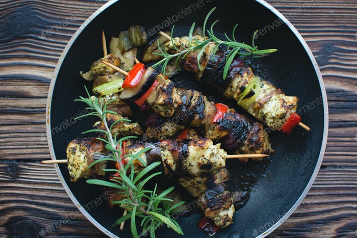 Grilled chicken skewers on a wooden background